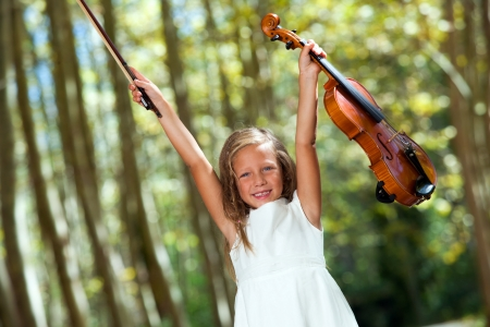 Portrait of happy violinist raising violin in the woods. photo