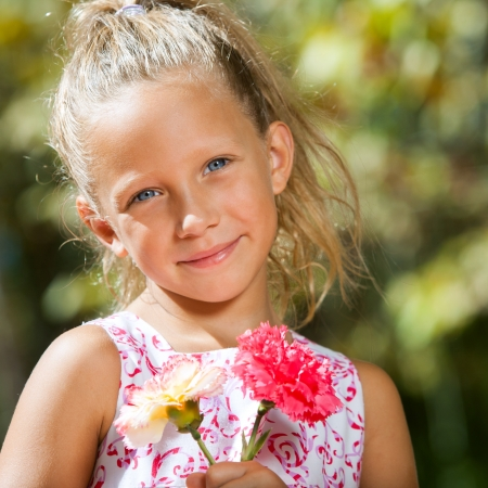 Close up portrait of sweet girl holding flowers in garden. Stock Photo - 15404440
