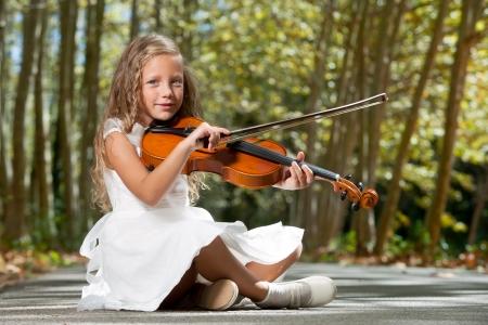 cello: Ritratto di giovane ragazza suonare il violino nella foresta.