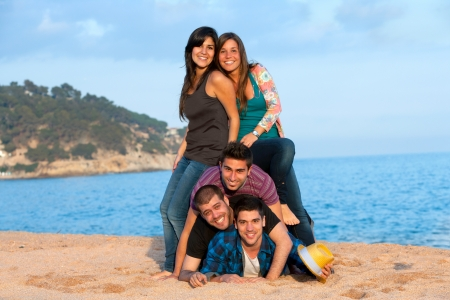 Portrait of young group of friends making a human pile on beach  photo