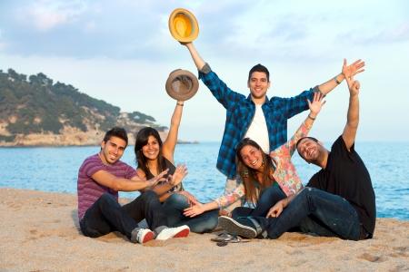 Groupe de jeunes amis à main levée au coucher du soleil plage Banque d'images