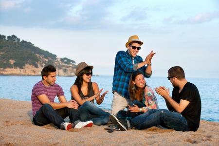 grupo de hombres: Grupo de j�venes amigos cantando y batiendo palmas en la playa Foto de archivo