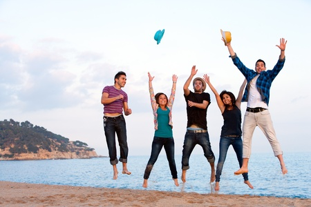 Group of energetic friends jumping high on beach