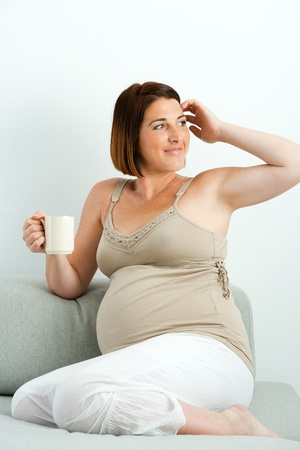 Attractive young pregnant woman sitting with coffee mug on couch  photo