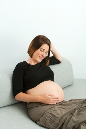 Attractive young pregnant mother sitting on couch at home Stock Photo - 15574604
