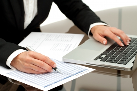 Close up of business womans hands working on laptop and accounting documents.