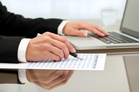 Close up of female hands doing paperwork with pen and laptop. Stock Photo - 15686207