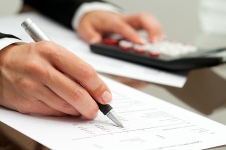 calculadora: Extreme close up de mano femenina con la pluma que se�ala en el documento de flujo de efectivo. Foto de archivo