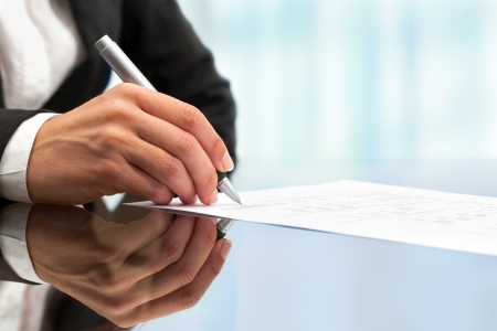 business writing: Extreme close up of female business hand signing document. Stock Photo