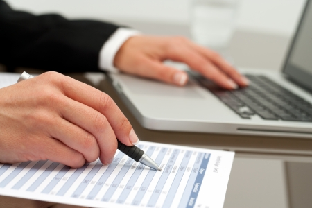 validating: Extreme close up of female business hands working on accounting document.