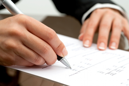 numers: Extreme close up of female hand pointing with pen on accounting document. Stock Photo