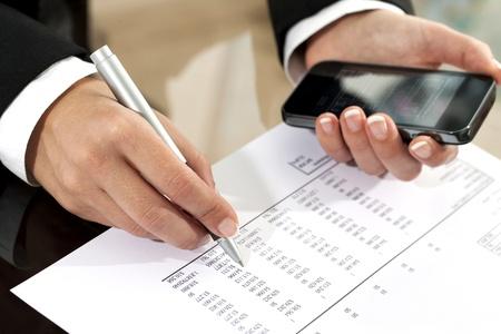 contabilidad: Primer plano de las manos femeninas revisi�n de los documentos contables con el tel�fono inteligente.