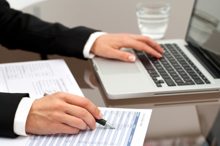 technology transaction: Close up of female hands reviewing accounting documents on table. Stock Photo