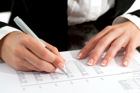 numers: Close up of female hands with pen reviewing accounting document. Stock Photo
