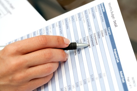 validating: Close up of female hand pointing with pen on financial document.