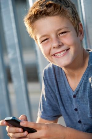 cute teen boy: Close up portrait of cute teen boy navigating on smart phone outdoors
