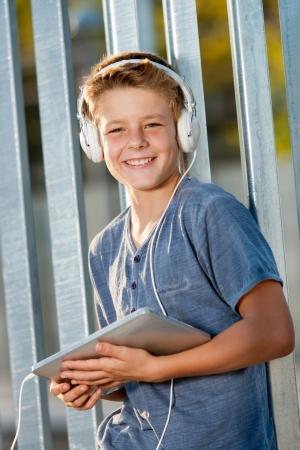 la escucha activa: Retrato de muchacho adolescente lindo que sostiene digital, tableta al aire libre