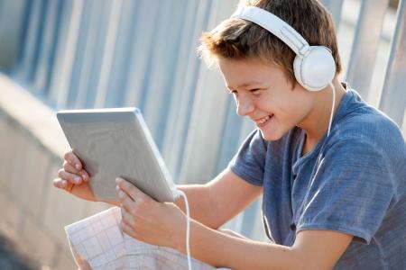 la escucha activa: Muchacho adolescente lindo escuchar música con auriculares y tabletas fuera