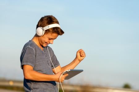 la escucha activa: Chico guapo adolescente feliz que escucha la música al aire libre en digital comprimido Foto de archivo