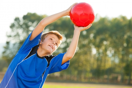 casualness: Young energetic teen boy jumping to red ball outdoors