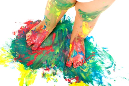 messy kids: Close up of babies feet on colorful mosaic painting.Isolated. Stock Photo