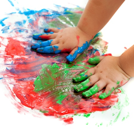 bright paintings: Close up of baby hands painting mosaic. Stock Photo