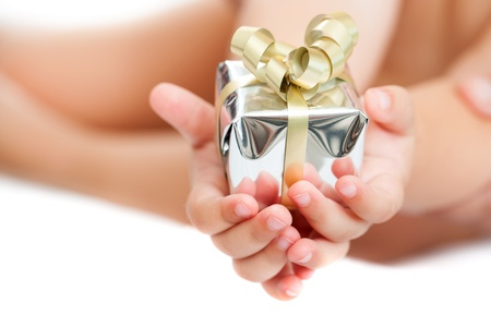 Macro close up of babies hands holding small present. Isolated. photo
