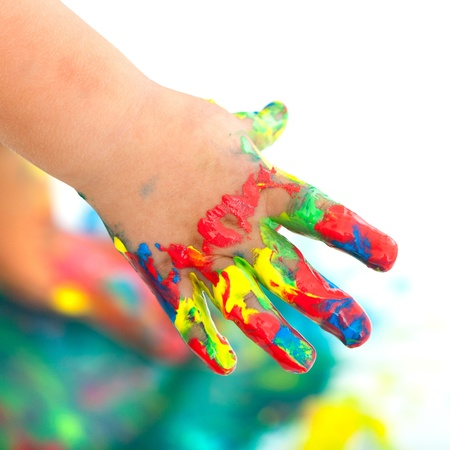 Close up of kids hand messed with colorful paint. Isolated on white.
