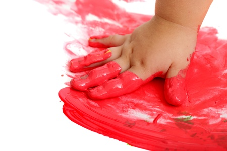 Close up of infant hand painting red mosaic.Isolated on white. photo
