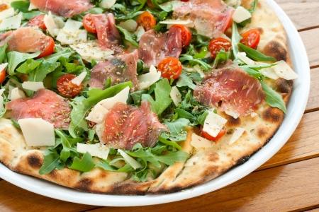 Close up of Italian prosciutto and rucola pizza. photo