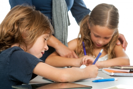 helping children: Close up of teacher supervising kids doing schoolwork. Stock Photo