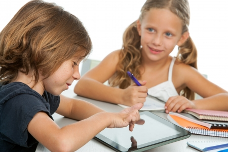 Portrait of two small kids doing homework on digital tablet.Isolated photo