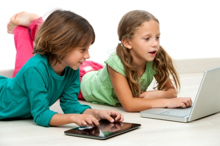 Two kids laying on floor with laptop and digital tablet. photo
