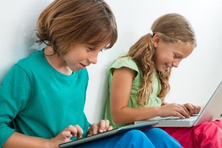 tarea escolar: Dos ni�os jugar y navegar por la web en la tableta digital y port�til. Foto de archivo