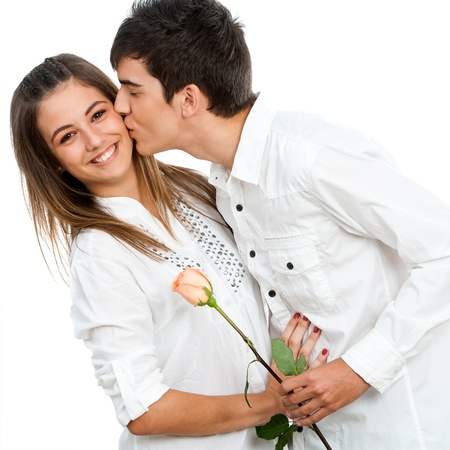 Close up of boy giving girlfriend a rose and romantic kiss.Isolated. photo