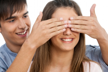 covering face: Close up of boy covering girlfriends eyes with hands .Isolated on white.
