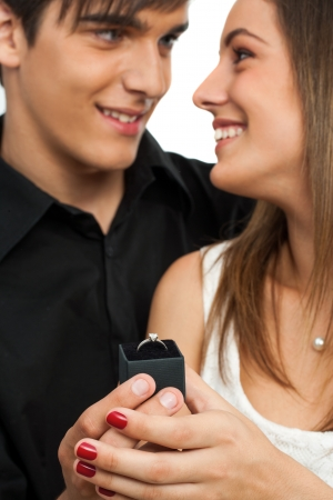 diamond ring: Close up of boy surprising girlfriend with diamond ring. Isolated on white. Stock Photo