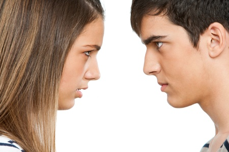 angry couple: Close up portrait of teen couple with angry face expression.Isolated.