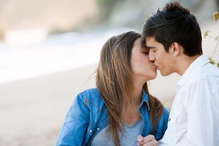 pareja besandose: Primer plano retrato del beso romántico en la playa.