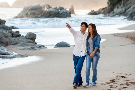 strolling: Young handsome teen couple taking romantic walk along beach.