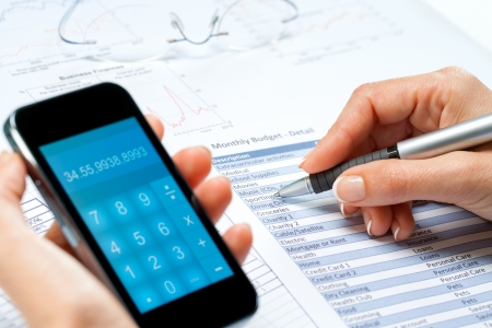 numers: macro close up of female hands calculating cash flow with smart phone.