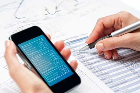 validating: Macro close up of female hands reviewing financial budget on smart phone. Stock Photo