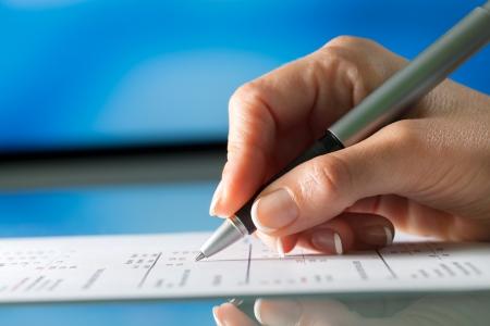 revisando documentos: Macro close up de documento firma hembra mano.