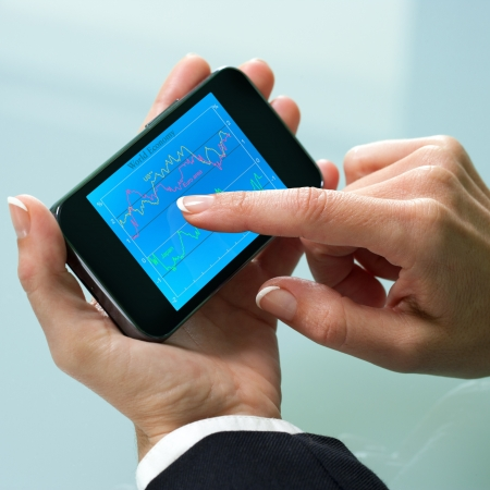 money matters: Macro close up of female hand reviewing business information on smart phone.