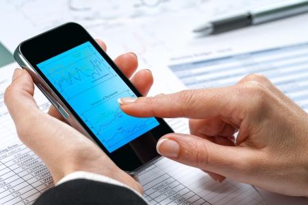 revisando documentos: Macro close up de mano femenina tocar negocio gráfico en el teléfono inteligente.
