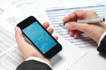 revisando documentos: Macro close up de las manos femeninas revisión contable en el teléfono inteligente.