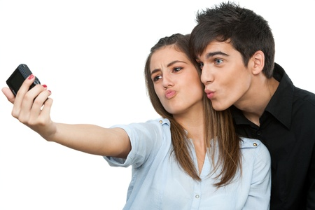 Cute young couple having fun taking self portrait.Isolated on white. Stock Photo - 16659986