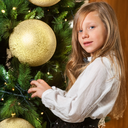 decorating christmas tree: Close up portrait of cute girl decorating christmas tree  Stock Photo