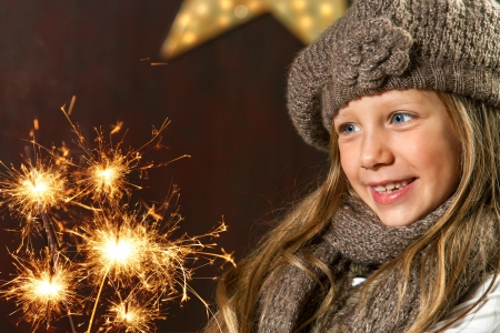new year party: Close up portrait of cute girl looking at festive fire sparks
