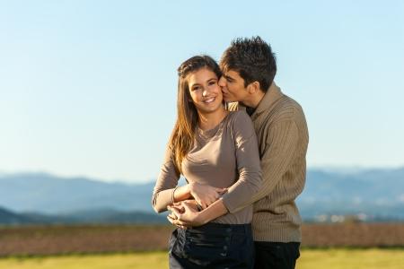 pareja de adolescentes: Close up retrato de novio besando a su novia en la mejilla en el campo. Foto de archivo